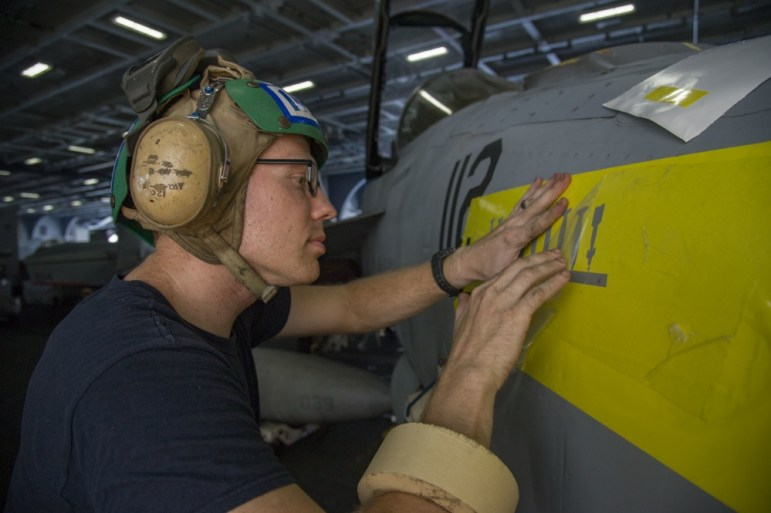 ARABIAN GULF (August 1) --Aviation Structural Mechanic 3rd Class William Atchison, from Yazoo City, Miss., prepares to stencil an F/A-18F Super Hornet assigned to the Fighting Swordsmen of Strike Fighter Squadron (VFA) 32 in the hangar bay of the aircraft carrier USS Dwight D. Eisenhower (CVN 69) (Ike). Ike and its Carrier Strike Group are deployed in support of Operation Inherent Resolve, maritime security operations and theater security cooperation efforts in the U.S. 5th Fleet area of operations.