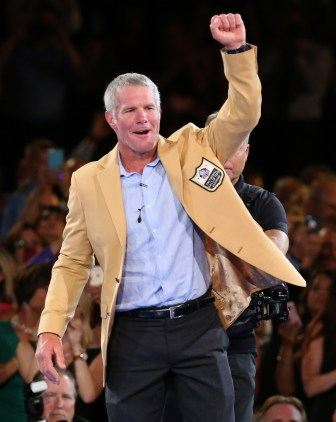 Brett Favre waves after receiving his gold jacket at the Pro Football Hall of Fame enshrinees' dinner on Thursday in Canton, Ohio.