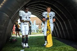 Cleveland High School players, with 'Battle of 61' across the front of their jerseys, prepare to take the field.