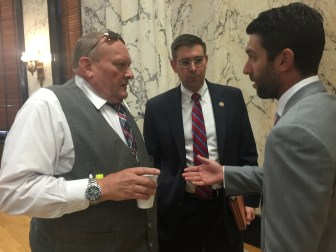 Sen. Terry Burton, R-Newton, and Rep. Andy Gipson, R-Braxton, talk with Daniel Harrison, a Wellcare Health Plus director, following the legislative budget session on Medicaid.