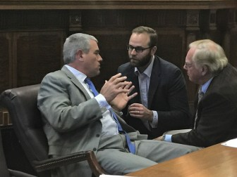 Speaker of the House Philip Gunn consults with his Chief of Staff Nathan Wells and Rep. John Read, chairman of the House Appropriations Committee, between hearings on Wednesday.
