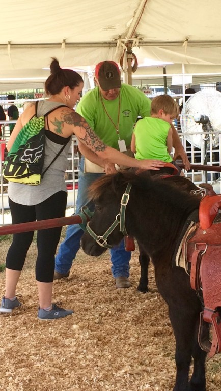 Boy enjoys a pony ride at the Mississippi State Fair