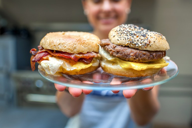 Marisol Doyle holds out breakfast bagel sandwiches, a popular menu item for Big River Bagels.
