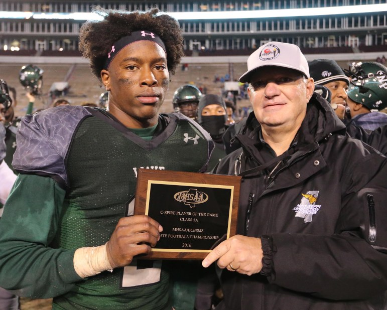 Marcus Murphy (left) receives the C Spire Player of the Game Award from Johnny Mims of the Mississippi Association of Coaches.