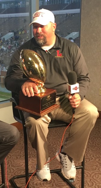 Michael Fair holds the golf ball State Championship trophy during post-game interview.