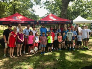 Ole Miss alumni, friends and family pose for a picture in front of the uinversity's tent in Chastain Park.
