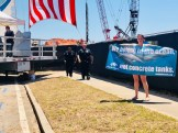 Police officers approach a woman holding a sign, protesting the enclosure of dolphins at the Mississippi Aquarium groundbreaking ceremony in Gulfport.