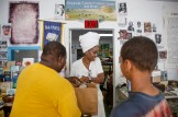 Ma'ati Jone Primm, owner of Marshall's Music and Bookstore, center, gives Malcolm Thompson, left, and his grandson Jonterrence Hanna, 13, purchased products from her store in the 600 block of North Farish Street in Jackon Friday June 29, 2018. The bookstore has been located on Farish Street for over 50 years.