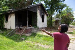 "Marilyn Martin points to a vacant home that is located next door to her home on Davis Street in the Farish Street Historic District Tuesday, July 3, 2018. ""It is a shame that no one has done anything about this property,"" said Martin."