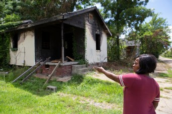 """Marilyn Martin points to a vacant home that is located next door to her home on Davis Street in the Farish Street Historic District Tuesday, July 3, 2018. """"It is a shame that no one has done anything about this property,"""" said Martin."""
