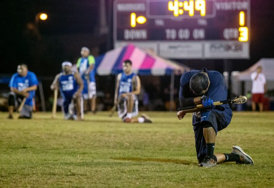 Players kneel after Mario Chickaway, 28, was injured during the World Series of Stickball at the Choctaw Indian Fair in Choctaw Wednesday, July 11, 2018.