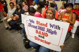 Anita Hampton holds a sign in support of her nephew, Forest Hill High School band director Demetri Jones, during the Jackson School Board meeting Tuesday, October 16, 2018.