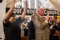 Audience members lift their hands in praise as Rev. William Barber II speaks during a Poor People's Campaign event at Greater Mt. Calvary Baptist Church Wednesday, October 24 in Jackson.