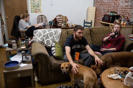 Kaitlyn Barton, left, finishes a day's work while her friend, Joe Greenberg, center, and roommate, Margaret Sumney, watch television while at home in Clarksdale Wednesday, October 31, 2018.