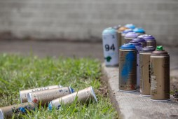 Used spray cans lay on the ground as artist work on murals during Mural Fest in downtown Jackson, Wednesday, April 17, 2019.