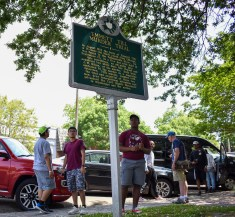 Students from New Jersey take a second to read the historical marker about Emmett Till's murder trial in front of the courthouse where the trial took place in Sumner, Miss.