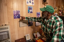 Anderson Jones Sr. points at a photo of him and his child on the wall in his living room.