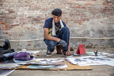 Michael Carter looks at his outlines before finishing his piece during the Paint the Town event in Clarksdale Tuesday, October 1, 2019.