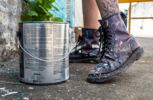 Erre's boots are covered with paint as she works on a mural during the Paint the Town event in Clarksdale Tuesday, October 1, 2019.