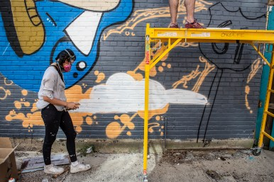 Artist Lik Mi works on a mural in Clarksdale in during the Paint the Town event in Clarksdale Tuesday, October 1, 2019.