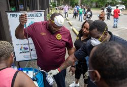 City employees help distribute hand sanitizer at Corner Market on Fortification Street in Jackson, Miss., Wednesday, April 8, 2020. The hand sanitizer was donated by Cathead Distillery.