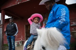 Kennedy gets a ride on a mini horse, assisted by her godfather Lester Brisby, in Bolivar County — 2019.