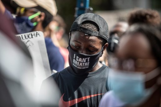 "A protester wears an ""I can't breathe"" mask during the Black Lives Matter protest in downtown Jackson, Miss., Saturday, June 6, 2020."