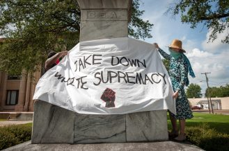 Protestors hang a sign on the Confederate statue outside the Bolivar County Courthouse in Cleveland, Mississippi on July 3, 2020.