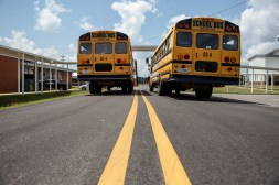School buses are parked near Neshoba County Central Middle School during the school's first day of class, Wednesday, August 5, 2020.