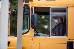 Ken Spears sits in the driver sit of a bus a he waits for Neshoba County School District students to board on the first day of school on Wednesday, August 5, 2020.