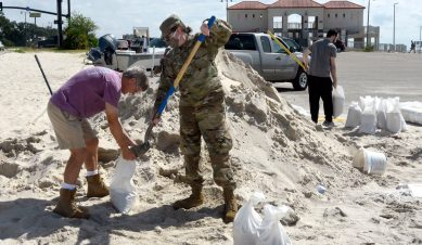 Melvin Wilson, left, and Robin Powell work together to fill sand bags near Ken Combs Pier in Gulfport. Much of the Mississippi Gulf Coast is under a hurricane warning as Tropical Storm Sally continues on its course.