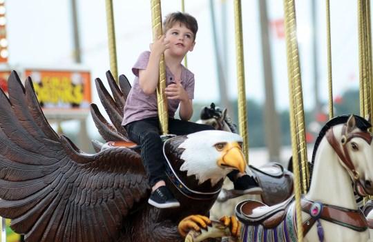 """He calls himself, Happy,"" said his grandmother. Happy, 4 of Brandon, enjoys a merry-go-round eagle flight."
