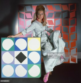 Model surrounded by artworks by Vasarely wearing Staron silk matelasse evening robe by Stella; earrings by Robert Originals; ring by Fabiola and sandals by I. Miller; Hair by Suga of Kenneth *** Local Caption ***