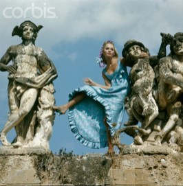 Bagheria, Sicily, Italy --- Model among the sculpture of the Villa Palagonia in Bagheria, Sicily, wearing an empire cut blue and mauve dress with ruffle at hem by Chester Weinberg. --- Image by © Condé Nast Archive/CORBIS