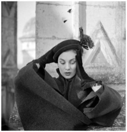 Suzanne Talbot et Jean Dessès (1904-1970). Chapeau et gants. Descendant des toques de François Ier, le chapeau de Suzanne Talbot est en feutre vert sombre piqué des plumes d'un faisan. Les gants de Jean Dessès sont en velours et drap, bordés de franges soyeuses. Château de Chambord (Loir-et-Cher), automne-hiver 1950. Photographie d'Henry Clarke (1918-1996), publiée dans l'Album du Figaro, 1950, 27, p.69. Galliera, musée de la Mode de la Ville de Paris. Dimensions : 6 x 6