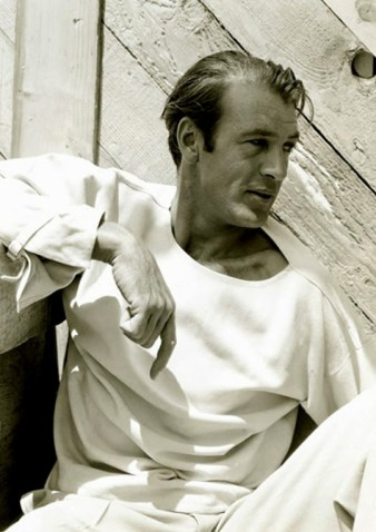 Duplicate: Actor Gary Cooper in white outfit sitting against wooden building