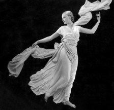Model wearing pale crepe romain pajamas by Vionnet holding long flowing scarf, in Grecian-style pose, 1931
