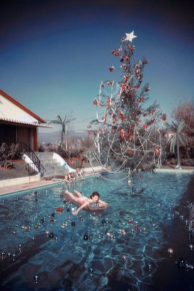 rita-aarons-wife-of-photographer-slim-aarons-swimming-in-a-pool-decorated-with-ornaments-and-a-christmas-tree-hollywood-california-1954