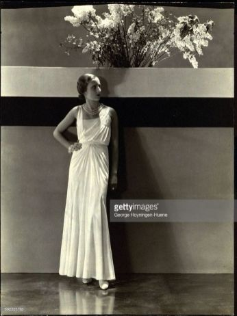 Model wearing long crepe romain dress by Maggy Rouff, with bracelet, and pearl necklace *** Local Caption ***