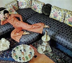 Model lounges in caftan by Talmack, shot by Howell Conant at the Moroccan embassy