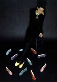 Model seated on stool surrounded by ballet slippers in various shades from Footlights. VOGUE MARCH 1944