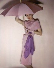 Model holding pink parasol wearing Traina-Norell's pink belted, button top rayon and wool,1944