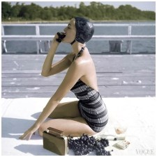 Model is wearing black and gray plaid halter swimsuit Vogue January 1953