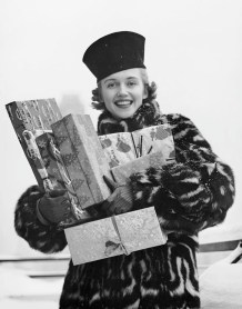 Woman carrying gifts for Christmas 1950s