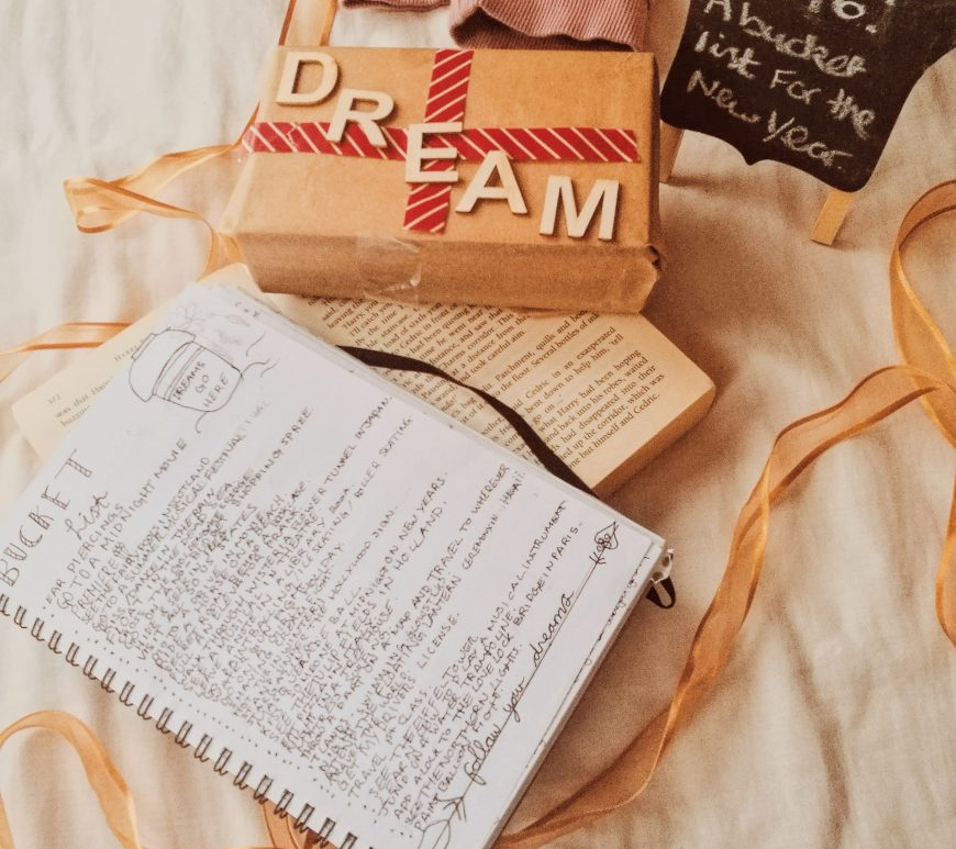bucket list for the new year with a notebook and wooden letters dream