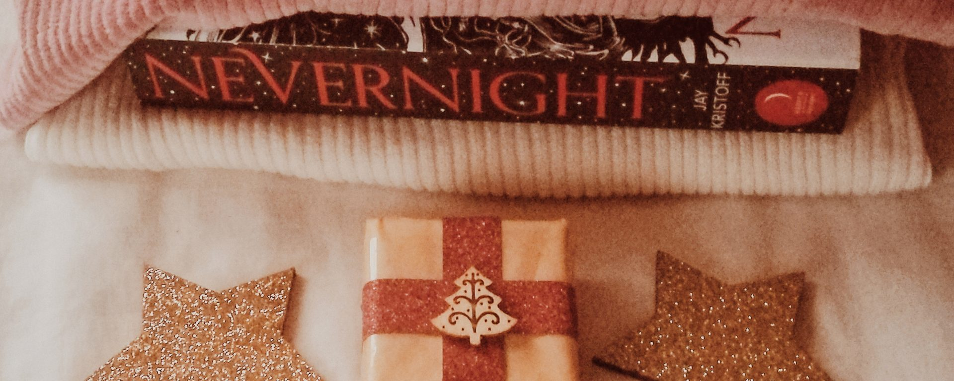small wrapped present, books, stars and sweaters for blog post secret santa gift ideas