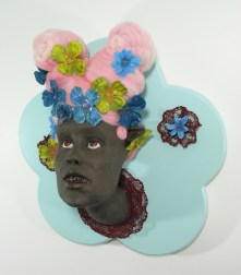 "Fashion Victim #6, 2010, clay, paint, resin, fake flowers, sand, lace, felted wool, wood, 19"" x 17"" x 12"""