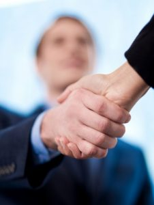 handshake with blurry face in background