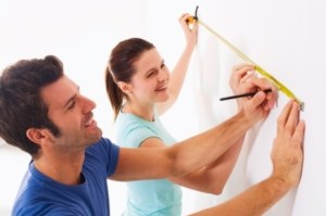 couple measuring a white wall