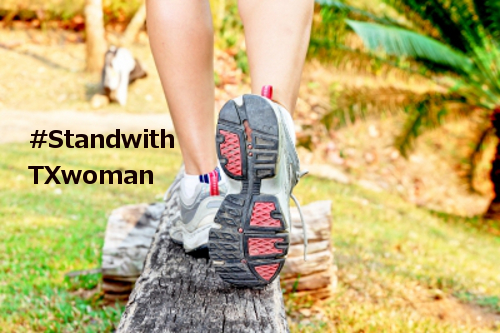 female legs in sneakers walking on a log